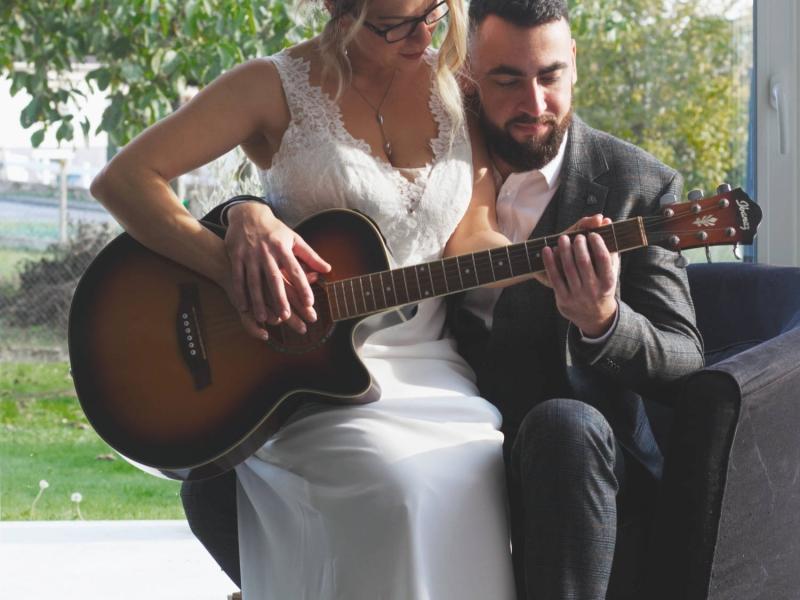 Couple marié joue la guitare ensemble
